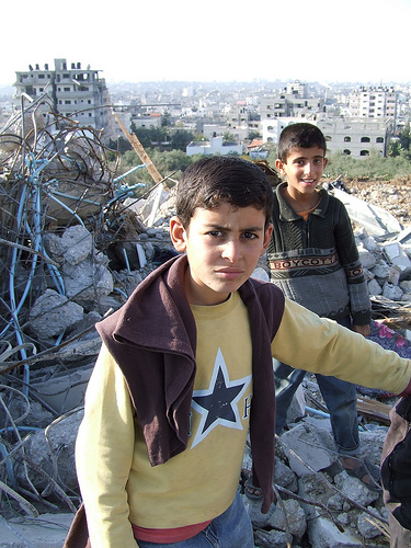 A Palestinian boy in the ruins of his home.
